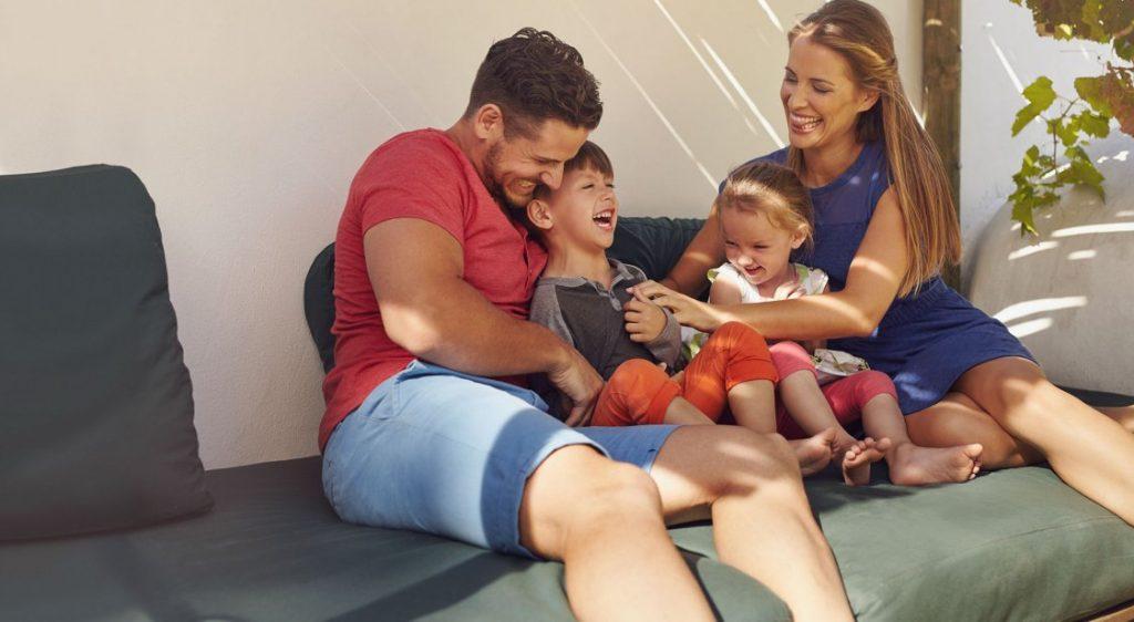 Family on couch enjoying multi room speaker system