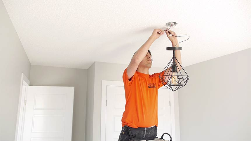 electrician-construction-labor-shortage-installing-fixture-in-ceiling