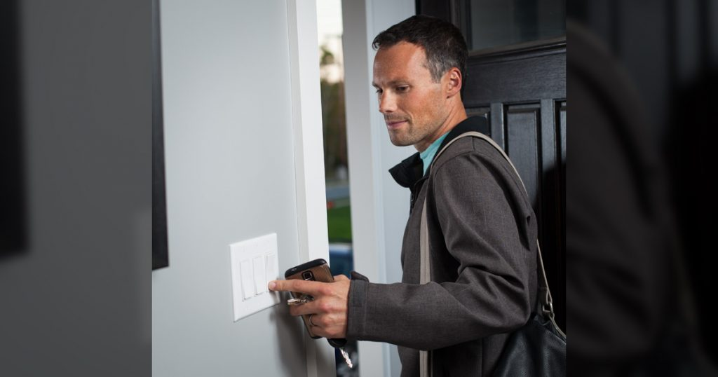 Image of man using a light switch remote