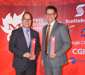 Image of Jim Qualie and James Keirstead accepting award for wireless remote wall switch